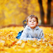 Little boy lying on the yellow leaves — Stock Photo