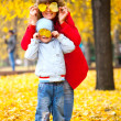 Child and mother with autumn leaves — Stock Photo