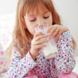 Child drinking milk in bed — Stock Photo #4149318