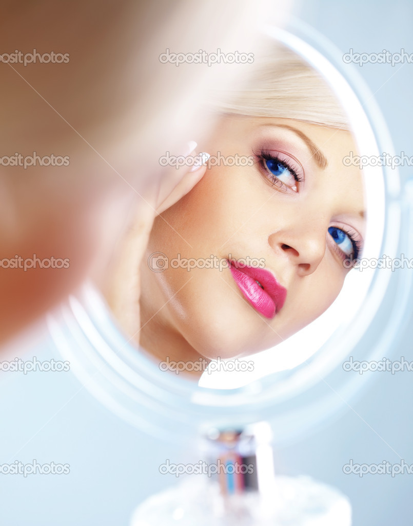 Young woman looking in cosmetic mirror — Foto Stock #4223029