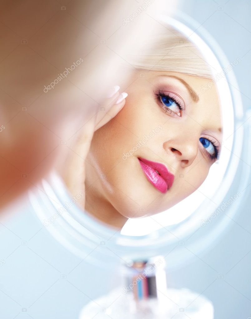 Young woman looking in cosmetic mirror — Stockfoto #4223029