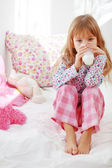 Child drinking milk in bed — Stock Photo