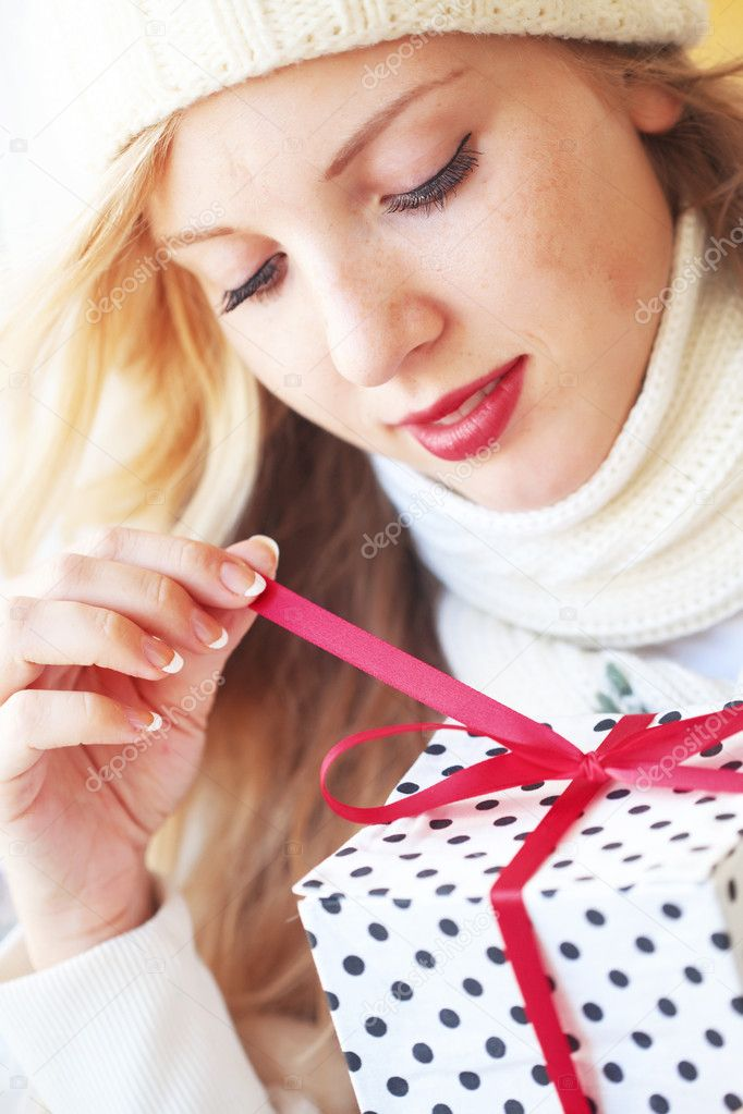 Portrait of cute young woman holding wrapped gift  Stock Photo #4732502