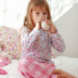 Stock Photo: Child drinking milk in bed