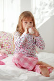 Child drinking milk in bed — Stockfoto
