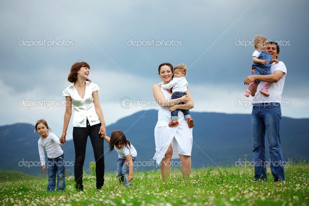 Group of happy parents with children resting in field — Stockfoto #5060389