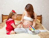 A daughter is painting on her mother`s belly — Stock Photo