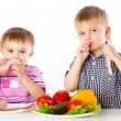 Boys and plates of vegetables and meat - Stock Photo