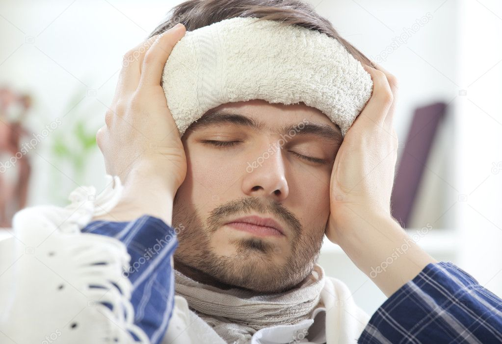 Sick male with wet towel on his forehead to reduce high fever — Stock Photo #4289512