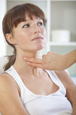 Doctor checking pulse on throat — Stock Photo