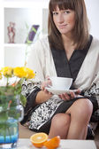 Vrouw in badjas en thee — Stockfoto