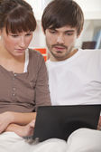 Couple with laptop at home — Stock Photo