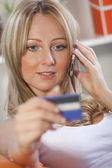 Woman with credit card and cell phone — Stock Photo