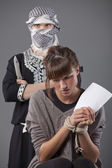 Female hostage and terrorist — Stock Photo