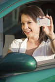Happy woman showing driving license — Stock Photo