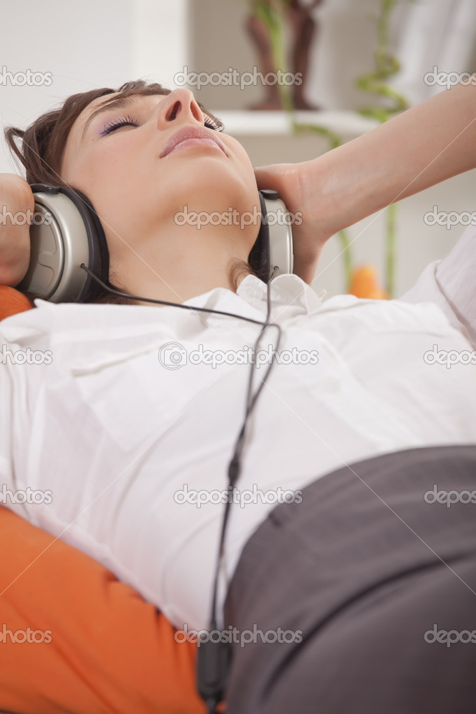 Woman in business suit relaxing at home and hearing music in earphones — Stock Photo #5103585