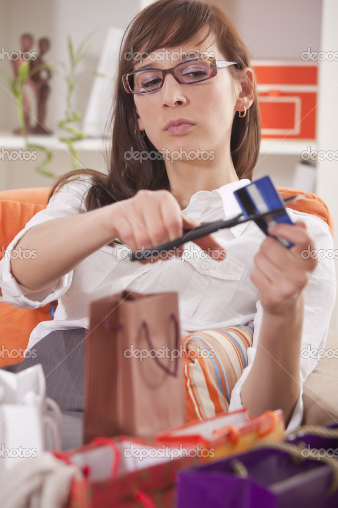 Shopaholic woman with shopping bags cutting her credit card   Stock Photo #5103615
