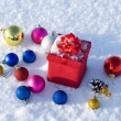 Red gift box on snow with christmas balls — Stock Photo