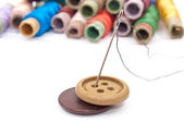 Buttons and threads with a needle — Stock Photo