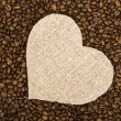 Sackcloth heart on coffee beans background — Stock Photo