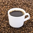 Cup of coffee in the coffee beans — Stok fotoğraf