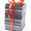 Pile of optical disc with red ribbon — Stock Photo #5352636
