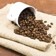 Coffee beans with white cup on sackcloth - Stock Photo