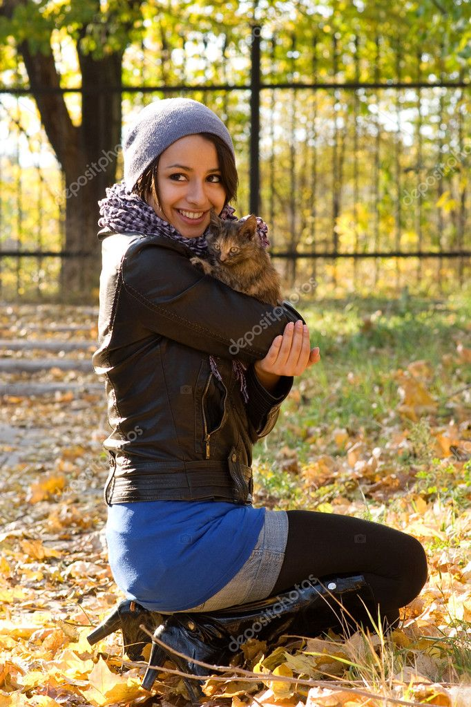 Attractive brunette chick and a kitten in the park at warm autumn day  Stock Photo #4723928