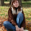 Girl sits in autumn park — Stock Photo