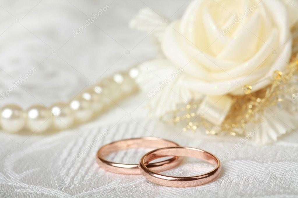 Fedi nuziali su sfondo di pizzo con collana doro in raso rosa e perla ...