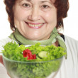 Mature woman with fresh salad — Stock Photo