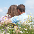 Loving couple sitting together in the middle of flowers — Stock Photo
