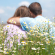 Stock Photo: Loving couple sitting together in the middle of flowers