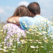 Loving couple sitting together in the middle of flowers - Stock Photo