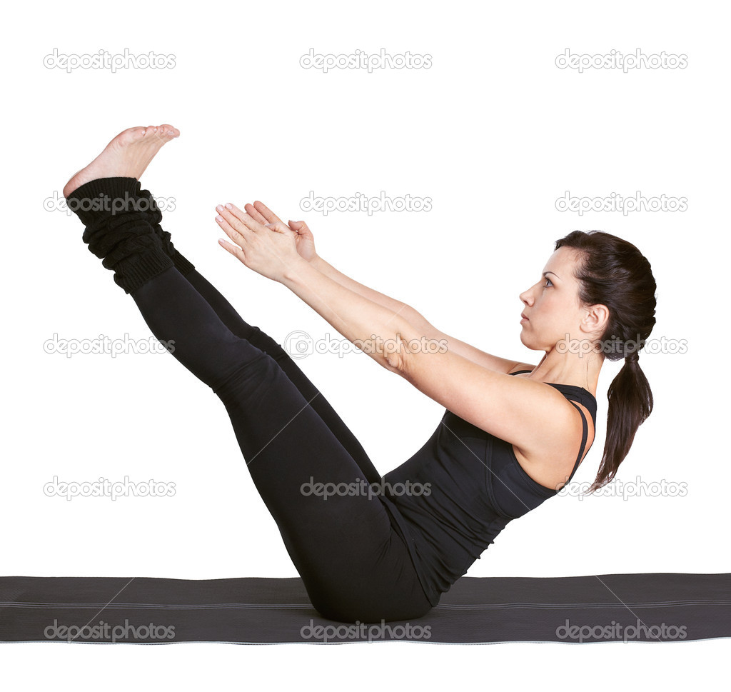 Full-length portrait of beautiful woman working out yoga excercise paripurna navasana (full boat pose) on fitness mat  Foto Stock #5235256