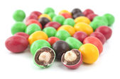 Pills with peanuts covered with multicolored glaze — Stock Photo