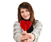 Girl with a heart-shaped candy — Stock Photo