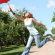 Smiling girl jumping with red umbrella - Stock Photo