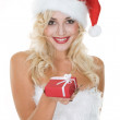 Beauty blonde girl in santa hat with gift — Stock Photo