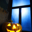 Halloween pumpkin in night on old wood room - Stock Photo