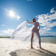 Woman in white on coast of sea - Stock Photo