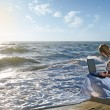 Royalty-Free Stock Photo: Blond girl using laptop on  sea