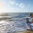 Blond girl using laptop on sea — Stock Photo