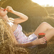 Beautiful woman sitting on the hay — Stock Photo