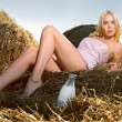 Woman sitting on the hay with a bottle of milk — Stock Photo #4990903