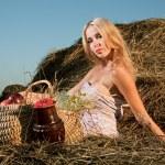 Beautiful woman sitting on the hay — Stock Photo #4990950
