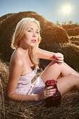 Kvinna sitter på hö och äta hallon — Stockfoto