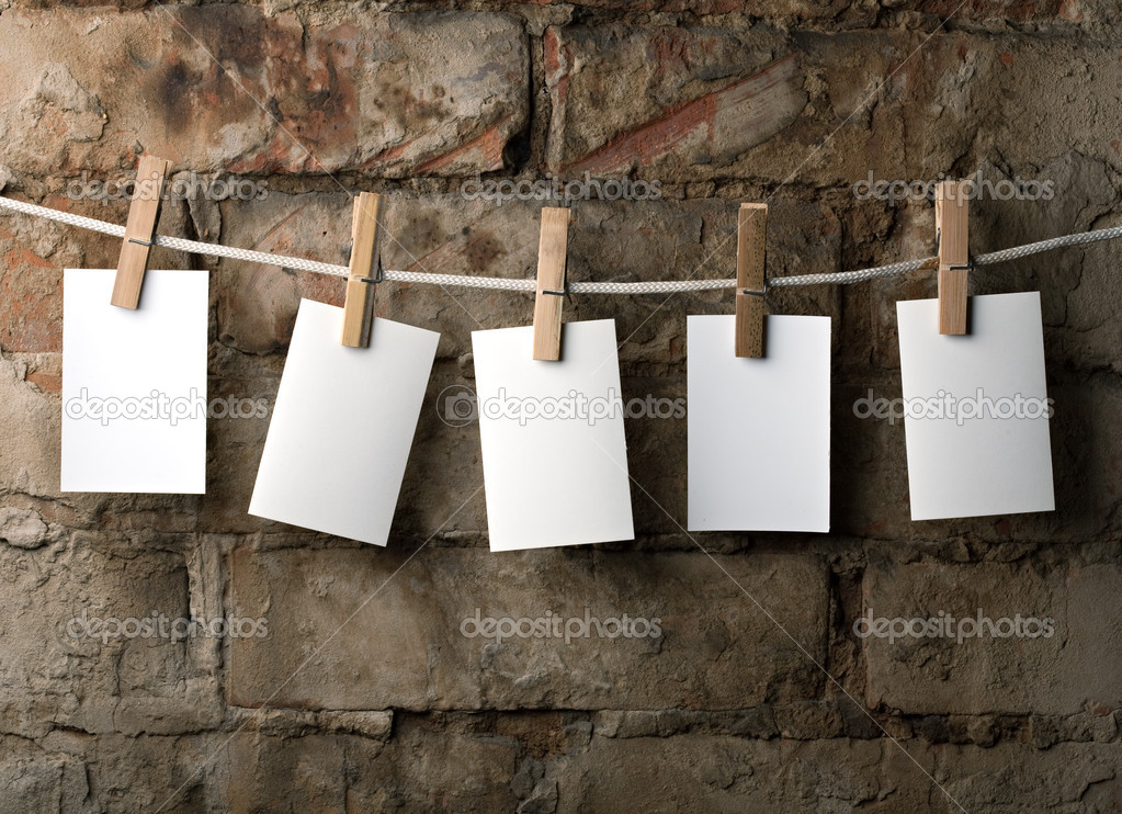Five photo paper attach to rope with clothes pins on brick background — Stock Photo #4990957