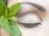 Macro shot of a female eye and fresh mint — Stock Photo