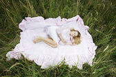 Woman lying on a sheet in field — Stock Photo